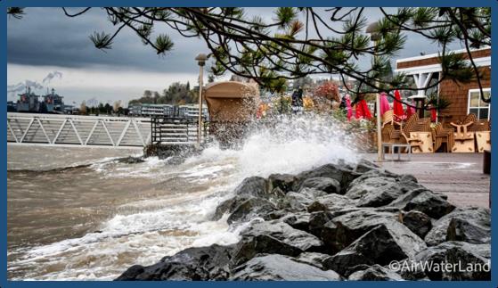 Wave crashing over beach barrier onto sidewalk during high tide.