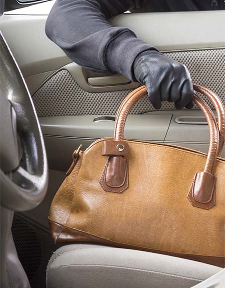 Image of purse being stolen from a vehicle.